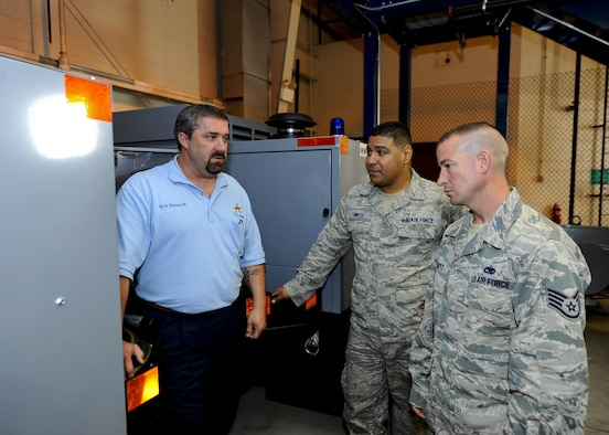 Rick Hammock, the 97th Maintenance Squadron aerospace ground equipment work leader, examines a mobile power generator for the KC-46A Pegasus with Staff Sgt. Detreck Ortiz (middle), a 22nd MXS aerospace ground equipment journeyman, and Staff Sgt. Allan Shurtz, a 931st MXS aerospace ground equipment journeyman, Oct. 27, 2015, at McConnell Air Force Base, Kan. Personnel from the three maintenance squadrons are working with the 22nd Logistics Readiness Squadron as maintenance equipment is shipped to McConnell in preparation of the arrival of the KC-46. (U.S. Air Force photo/Senior Airman Victor J. Caputo)