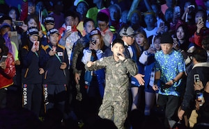 Korean athletes snap photos of pop star Kim Jaejoong as he sings Arirang in the center of the stadium during the closing ceremony for the CISM World Games Oct. 11, 2015, in MunGyeong, South Korea.