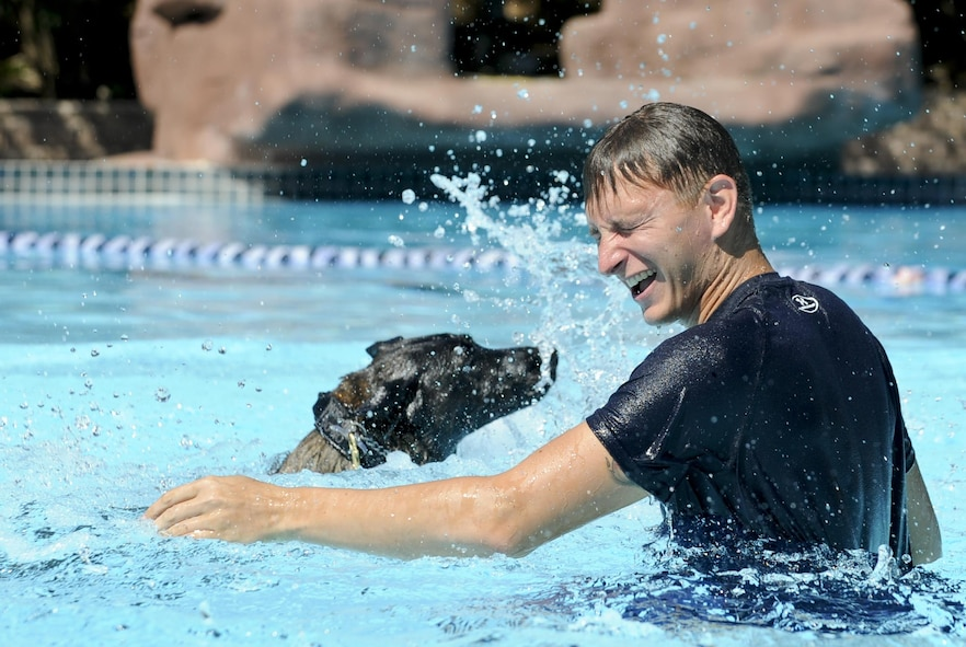 Staff Sgt. Jenings Casey, a 6th Security Forces Squadron military working dog handler, and military working dog Branco splash in a wave pool after a water aggression training exercise at a water park in Tampa, Fla., Oct. 15, 2015. The water aggression training offers a unique opportunity for working dogs to become familiar with water. (U.S. Air Force photo/Airman 1st Class Mariette M. Adams)