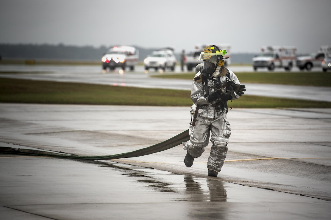 A firefighter from the 23rd Civil Engineer Squadron runs toward a simulated aircraft crash scene during a major accident response exercise Oct. 27, 2015, at Moody Air Force Base, Ga. Once the firefighters were able to put out the fire and secure the scene, they were able to assist in removing patients from the area. (U.S. Air Force photo/Senior Airman Ryan Callaghan)
