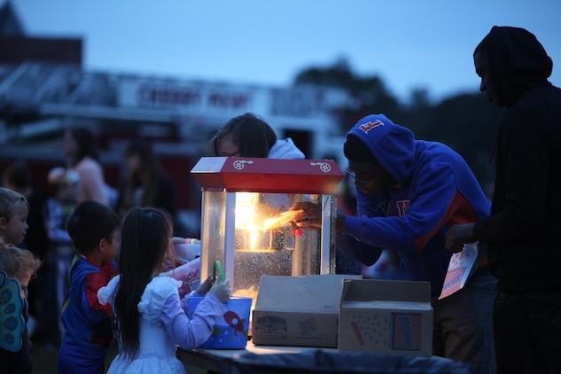 Volunteers with Marine Wing Headquarters Squadron 2 and Marine Aircraft Group 14 serve popcorn to children during the 3rd Annual Trunk-or-Treat at Marine Corps Air Station Cherry Point, N.C., Oct. 26, 2015. The event was hosted by Marine Wing Headquarters Squadron 2 and Marine Aircraft Group 14 family readiness officers to encourage families to come together in a safe and fun environment to trick-or-treat. During the event, service members, spouses and family members played games, watched Halloween movies and went trick-or-treating. (U.S. Marine Corps photo by Cpl. U. B. Roberts/Released.)