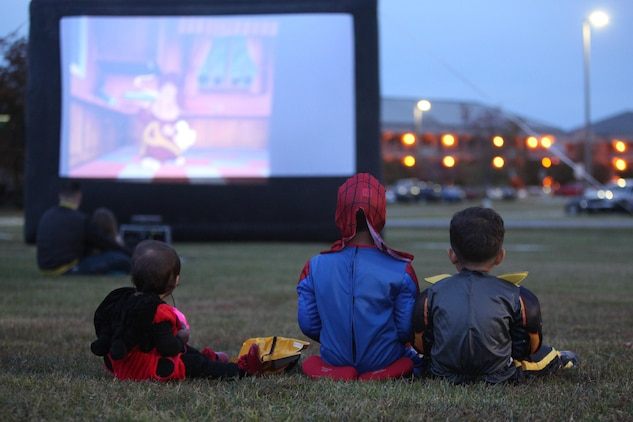 """Service members, spouses and families watch a movie during the 3rd Annual Trunk-or-Treat at Marine Corps Air Station Cherry Point, N.C., Oct. 26, 2015. Families and spouses watched Halloween themed movies like """"The Ghost of Lord Farquaad"""" and """"Alvin and the Chipmunks: Halloween collection."""" The event was hosted by Marine Wing Headquarters Squadron 2 and Marine Aircraft Group 14 to allow family members to get together and celebrate Halloween in a safe and fun environment.   (U.S. Marine Corps photo by Cpl. U. B. Roberts/Released.)"""