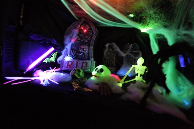 """Families decorated the trunk of their vehicles with various themes for the 3rd Annual Trunk or Treat event at Marine Corps Air Station Cherry Point, N.C., Oct. 26, 2015. Families transformed the trunks of their vehicles into replicated hit movies for exciting themes like """"Star Wars,"""" """"Alice and Wonderland"""" and """"It's the great Pumpkin: Charlie Brown,"""" During the event, service members, spouses and family members played games, watched Halloween movies and went trick-or-treating. The event was hosted by Marine Wing Headquarters Squadron 2 and Marine Aircraft Group 14 family readiness officers to encourage families to come together in a safe and fun environment to trick-or-treat. (U.S. Marine Corps photo by Cpl. U. B. Roberts/Released.)"""