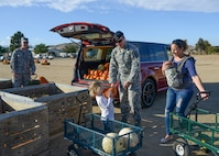 Master Sgt. Scott Harris, 412th Security Forces Squadron, loaded pumpkins into their vehicle at Tapia's Pumpkin Patch with the help of his daughter, Ava, for the squadron's Halloween party. (U.S. Air Force photo by Rebecca Amber)