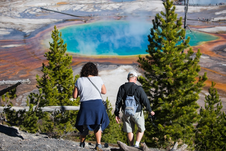 A French couple descends a hill near the Fairy Falls Trailhead after enjoying the view of Grand Prismatic Spring at Yellowstone National Park, Wyoming Oct. 10, 2015. The spring is the third largest in the world and owes its vibrant array of colors to heat-loving bacteria residing in its warm water. (U.S. Air Force photo by Airman 1st Class Connor J. Marth)
