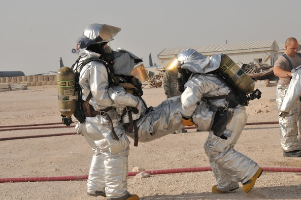 Two 379th Expeditionary Civil Engineer Squadron firefighters carry one of their fellow firefighters out of a simulated burning building during an interagency exercise in Al Udeid Air Base, Qatar Oct. 27. The injured firefighter stepped on a mock explosive device which required him to be rescued from the building. The interagency exercise featured professionals from three 379th Air Expeditionary Wing units including explosive ordnance technicians, security forces patrolmen and firefighters. (U.S. Air Force photo by Tech. Sgt. Terrica Y. Jones/Released)