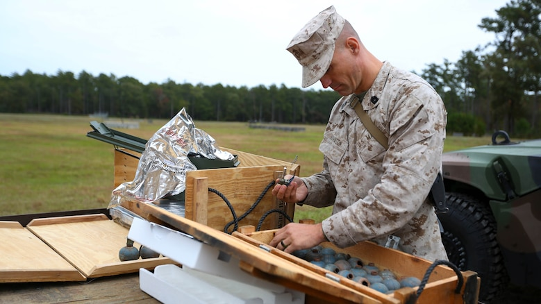 Master Sgt. Donald Johnson prepares M67 fragmentation grenades during a grenade and MK-19 Grenade Launcher range at Marine Corps Base Camp Lejeune, N.C., Oct. 28, 2015. More than 70 Marines with 2nd Low Altitude Air Defense Battalion took turns handling the MK19 and handheld grenades during the familiarization range. The range offered Marines the opportunity to build confidence and proficiency skills on some of the crew-served weapons they operate while providing security in a deployed environment. Johnson is the 24th Marine Expeditionary Unit Detachment staff noncommissioned officer in charge with the battalion.