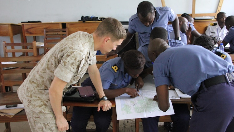 """U.S. Marine Capt. Jeremy Phillips, the intelligence security cooperation Officer with Special-Purpose Marine Air-Ground Task Force Crisis Response-Africa, discusses intelligence gathering with Ghanaia Navy intelligence at Ghana's Navy Trade Training School in Sekondi, Ghana, Oct. 19. U.S. forces completed a Tactical Intelligence Support To Maritime Operations Centers """"train-the-trainer"""" course for the Ghanaian Navy from Oct. 12-23. This two-week introduction to intelligence was the first of four planned for the fiscal year.  U.S. Navy and Marine Corps service members taught Sixteen Ghanaian sailors, along with two senior members of Ghana's Marine Police Unit of the Ghana Police Service. The course was designed as both an introduction to the intelligence process, particularly in support of their MOCs, and to prepare the students to become intelligence instructors for the Ghanaian Navy's internal intelligence courses."""
