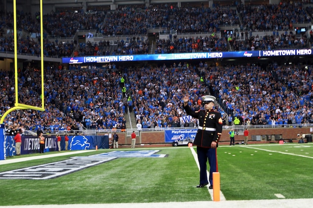 U.S. Marine Sgt. Benjamin J. Annarino waves to more than 60,000 cheering fans during a Detroit Lions football game Oct. 20, 2015, at Ford Field in Detroit. Annarino was honored as the game's Hometown Hero during a break in play in the third quarter. Annarino is a canvassing recruiter for Recruiting Station Detroit and a Livonia, Michigan, native. (U.S. Marine Corps photo by Sgt. J. R. Heins/ Released)