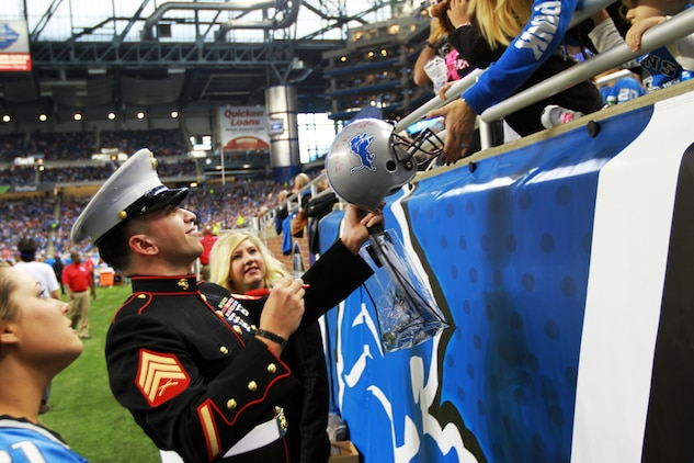 U.S. Marine Sgt. Benjamin J. Annarino signs a fan's helmet during a Detroit Lions football game Oct. 20, 2015, at Ford Field in Detroit. Annarino was honored as the game's Hometown Hero during a break in play in the third quarter. Annarino  is a canvassing recruiter for Recruiting Station Detroit and a Livonia, Michigan, native. (U.S. Marine Corps photo by Sgt. J. R. Heins/ Released)