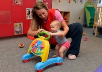Zelia Mersinger, 56th Force Support Squadron child development center educational technician, helps a baby onto her walker at the Child Development Center at Luke Air Force Base, Ariz., Oct. 7, 2015. The CDC accepts children with reservations and a space-available, drop-in basis. A child may stay for a few hours or spend the entire day on a limited basis. The center also has an active sublet program for parents seeking temporary care. (U.S. Air Force photo by Senior Airman Devante Williams)