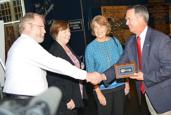 Warner Robins Mayor Randy Toms (right) shakes hands with Frank Guilfoyle as his sisters, Jane Guilfoyle Ward and Anne Guilfoyle Charlton, look on. The siblings are the grandchildren of Gen. Augustine Warner Robins, who both the town and the base are named after. Toms presented them with the key to the city. (U.S. Air Force photo/Ray Crayton)