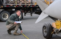 U.S. Air Force Tech. Sgt. Rebecca Morin, the 354th Logistics Readiness Squadron noncommissioned officer in charge of air terminal operations, measures a fuel tank Oct. 28, 2015, at Eielson Air Force Base, Alaska. Morin verified the fuel tank length to find the center of balance for the cargo. (U.S. Air Force photo by Airman 1st Class Cassandra Whitman/Released)