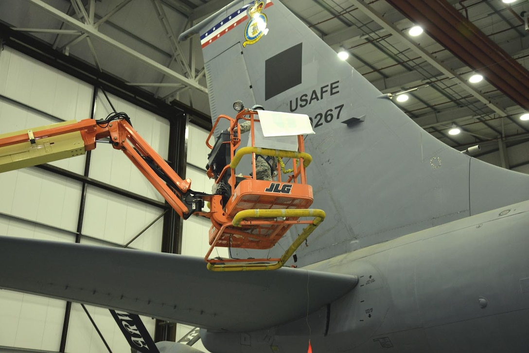 "U.S. Air Force Staff Sgt. Adam Denham, 100th Maintenance Squadron aircraft structural maintenance craftsman, uses a boom lift to place the ""D"" decal on top of a black square to form the ""Square D"" on the tail of a KC-135 Stratotanker Oct. 21, 2015, on RAF Mildenhall, England. The jet, formerly from McConnell Air Force Base, Kan., has been reassigned to RAF Mildenhall and underwent a full isochronal inspection. The jet has now been repainted and given the Square D markings. (U.S. Air Force photo by Karen Abeyasekere/Released)"