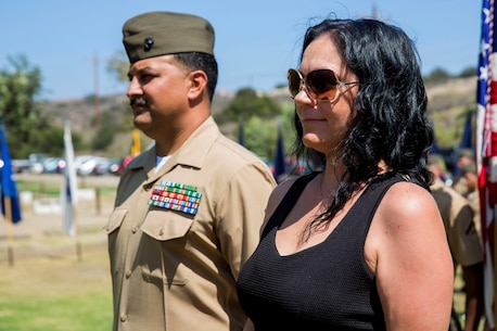 "Rosamond, Calif., native, Christina Lujan, wife of Gunnery Sgt. Pedro ""Pete"" Lujan, the cyber security chief for 9th Communication Battalion, I Marine Expeditionary Force Headquarters Group, joins her husband in formation to receive a certificate of appreciation during Pedro's retirement ceremony aboard Marine Corps Base Camp Pendleton, Calif., Aug. 21, 2015. Pedro said they have been together since their freshman year of high school and have now been married for approximately 19 years. His family has supported him through approximately five years' worth of deployments throughout his 20-year career."
