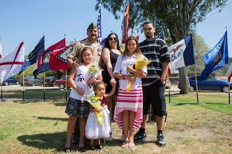 "Rosamond, Calif., native, Gunnery Sgt. Pedro ""Pete"" Lujan, the cyber security chief for 9th Communication Battalion, I Marine Expeditionary Force Headquarters Group, is joined by his family during his retirement ceremony aboard Marine Corps Base Camp Pendleton, Calif., Aug. 21, 2015. Lujan's wife, Christina, has been with him since their freshman year of high school and they have been married for approximately 19 years. Lujan's family has supported him through approximately five years' worth of deployments throughout his 20-year career."