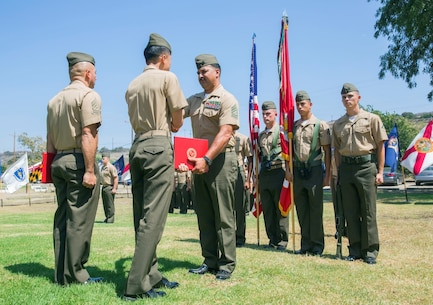"Rosamond, Calif., native, Gunnery Sgt. Pedro ""Pete"" Lujan, the cyber security chief for 9th Communication Battalion, I Marine Expeditionary Force Headquarters Group, receives his certificate from 1st Lt. Yinan Yang, the assistant operations officer for 9th Comm., during Lujan's retirement ceremony aboard Marine Corps Base Camp Pendleton, Calif., Aug. 21, 2015. Lujan said he credits his success to the way the Marine Corps takes care of the Marines who serve."