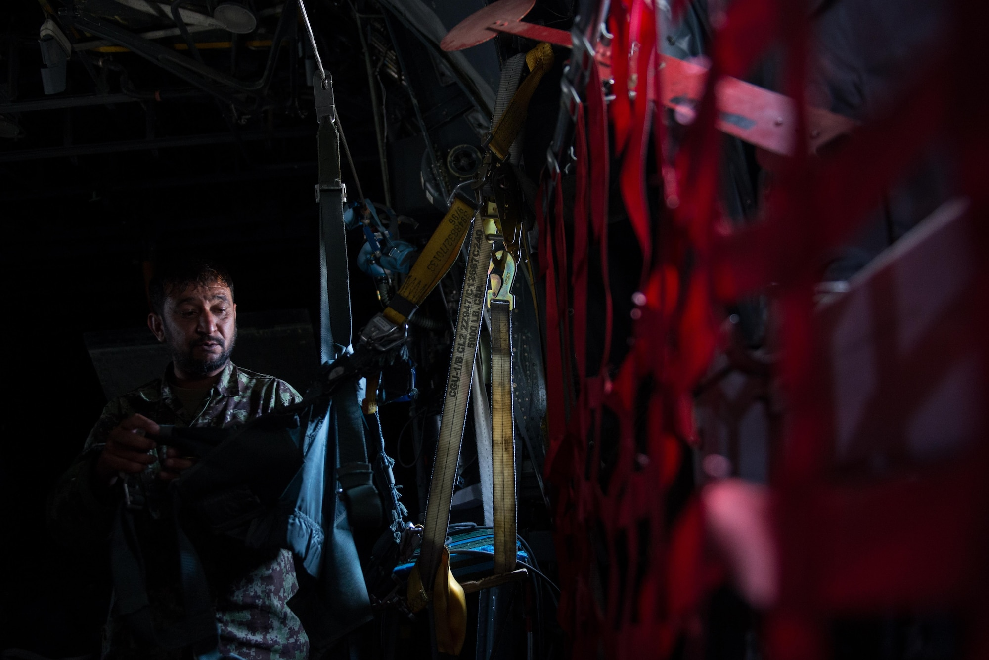An Afghan airman inspects aircrew flight equipment aboard an Afghan C-130H Hercules aircraft during a training session with U.S. Airmen from the 455th Air Expeditionary Wing at Hamid Karzai International Airport, Kabul, Afghanistan, Aug. 29, 2015. Airmen with the 455th AEW visited Forward Operating Base Oqab and Hamid Karzai International Airport to share their aircrew flight equipment knowledge with their Afghan counterparts and also assist Train, Advice, Assist Command-Air with keeping Coalition AFE equipment current. (U.S. Air Force photo by Tech. Sgt. Joseph Swafford/Released)