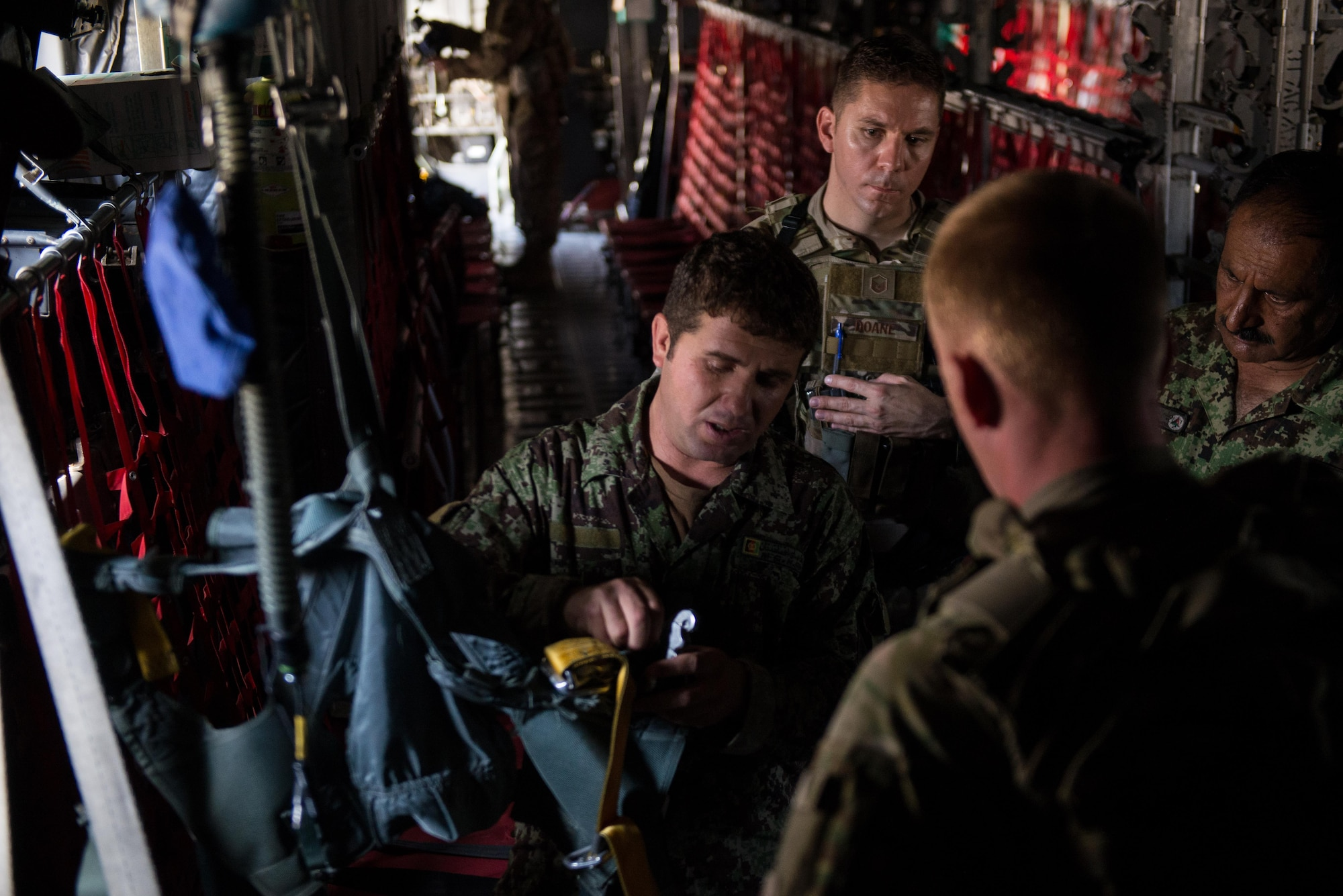An Afghan airman demonstrates his aircrew flight equipment knowledge to U.S. Airmen from the 455th Air Expeditionary Wing and Train, Advice, Assist Command-Air aboard an Afghan C-130H Hercules at Hamid Karzai International Airport, Kabul, Afghanistan, Aug. 29, 2015. Airmen with the 455th AEW visited Forward Operating Base Oqab and Hamid Karzai International Airport to share their aircrew flight equipment knowledge with their Afghan counterparts and also assist TAAC-Air with keeping Coalition AFE equipment current. (U.S. Air Force photo by Tech. Sgt. Joseph Swafford/Released)