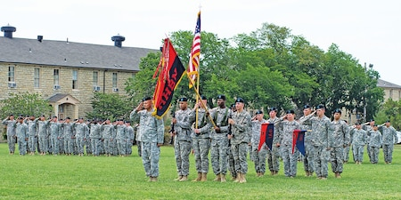 Col. Thomas Hipskind, center left, salutes one last time as commander of Division Headquarters and Headquarters Battalion, 1st Infantry Division, during a change of command ceremony for the battalion August 4 at Fort Riley.  Hipskind relinquished command to Lt. Col. Jeffrey Bracco during the ceremony.