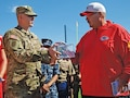 """Sgt. 1st Class Abram Pinnington, DHHB, 1st Inf. Div., presents Andy Reid, Kansas City Chiefs head coach, with a """"Big Red One"""" helmet signed by Maj. Gen. Wayne W. Grigsby Jr., division commanding general, Aug. 19 during the final day of the Kansas City Chiefs' 2015 Training Camp in St. Joseph, Missouri."""