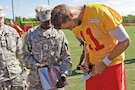 Alex Smith, Kansas City Chiefs quarterback, signs an autograph for Spc. Sam Kosgei, Headquarters Support Company, Division Headquarters and Headquarters Battalion, 1st Infantry Division, Aug. 19 at the team's 2015 Training Camp in St. Joseph, Missouri. Ten 1st Inf. Div. and Fort Riley Soldiers were selected to travel to Missouri Western State University to watch the team's practice. They were among the 100 service members representing the Army, Marines, Air Force and Navy who participated in the team's Military Appreciation Day.