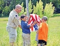 Sgt. 1st Class Patrick Sullivan, Division Headquarters and Headquarters Battalion, 1st Infantry Division helps Webelos members raise the flag to kick off the Cub Scout Pack 660 camping event.