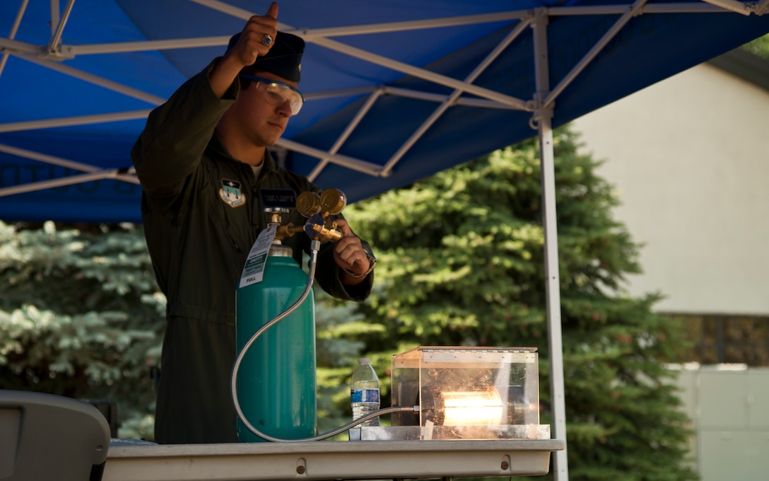 PETERSON AIR FORCE BASE, Colo. – Cadet Tyler Hudson, U.S. Air Force Academy, demonstrates how jet fuel works during the Science, Technology, Engineering, and Math event at the Peterson Air and Space Museum, Aug. 29, 2015. Volunteers from Peterson AFB and other surrounding bases came together to make the annual event a success promoting STEM topics through booths demonstrating electricity, mineral mining, rocket launching, dinosaurs and more. (U.S. Air Force photo by Senior Airman Tiffany DeNault)