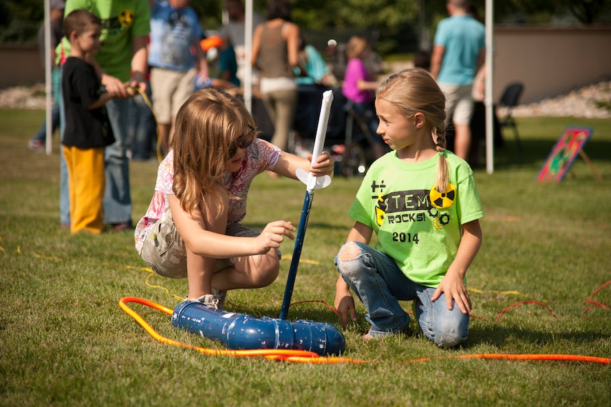 PETERSON AIR FORCE BASE, Colo. – Torrie Sheard and Aurora Mayo prepare their custom designed rocket for launch during the Science, Technology, Engineering, and Math event at the Peterson Air and Space Museum, Aug. 29, 2015. Rocket building/launching was one of many activities present at the annual event promoting STEM topics to military children. (U.S. Air Force photo by Senior Airman Tiffany DeNault)