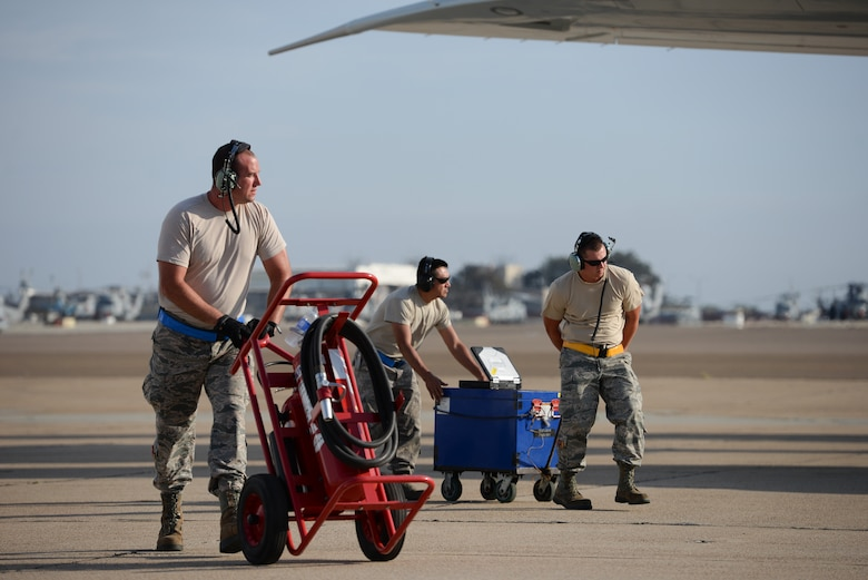Master Sgt. Justin Sproles, a communication and navigation specialist assigned to the 513th Aircraft Maintenance Squadron, pushes a fire extinguisher into place Aug. 24 at Naval Air Station North Island in Coronado, Calif., after an E-3C Sentry completed a training mission as part of Joint Task Force Exercise 2015. The 513th maintenance reservists accompany every off-station training mission to provide routine checks as well as repairs if needed. (U.S. Air Force photo by Staff Sgt. Caleb Wanzer)