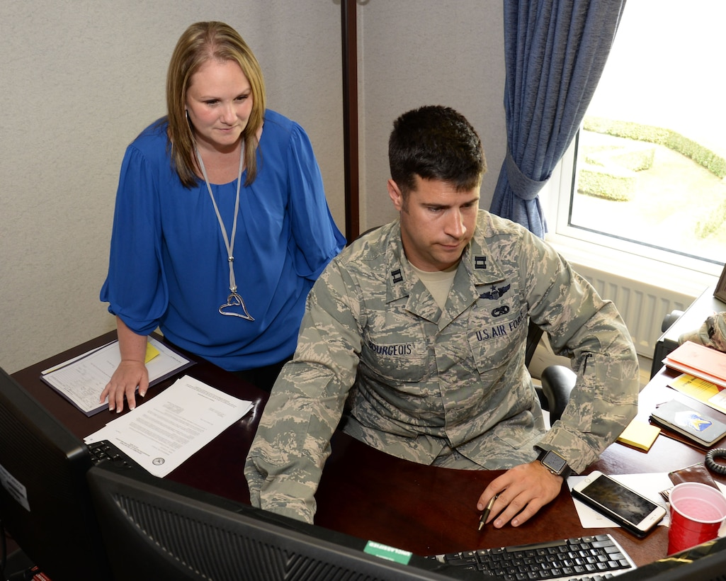 Marlene Teekell, left, 352nd Special Operations Wing commander's secretary and protocol liaison officer and U.S. Air Force Capt. Todd Bourgeois, 352nd SOW executive officer, make arrangements for their commander's upcoming travel plans Aug. 20, 2015, on RAF Mildenhall, England. Teekell works closely with the executive officers to ensure wing management is able to take care of their duties. (U.S. Air Force photo by Gina Randall/Released)