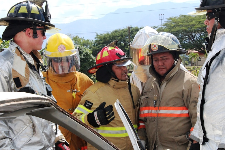 SOTO CANO AIR BASE, Honduras - Miguel Matus, a firefighter from the Belize National Fire Service (center), translates from English to Spanish for his team members from different Central American nations, during a vehicle extrication practice for CENTAM SMOKE, Aug. 27, 2015. CENTAM SMOKE, a quarterly exercise hosted by Joint Task Force-Bravo at Soto Cano Air Base, Honduras, allows participants to share experiences and knowledge in order to develop lasting relationships and to improve interoperability between nations.  (U.S. Army photo by Maria Pinel)