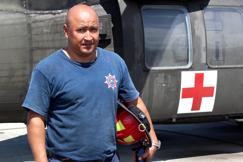 SOTO CANO AIR BASE, Honduras - Miguel Matus, a firefighter with the Belize National Fire Service, poses for a photo next to a Blackhawk UH-60 helicopter after practicing loading and unloading patients Aug. 27, 2015,during CENTAM SMOKE, a quarterly firefighting exercise hosted by Joint Task Force-Bravo at Soto Cano Air Base, Honduras. CENTAM SMOKE allows firefighters from Central America to train with U.S. firefighters in structural fires, aircraft fires, emergency evacuation and vehicle extractions to build partnership and improve interoperability. (U.S. Army photo by Maria Pinel)