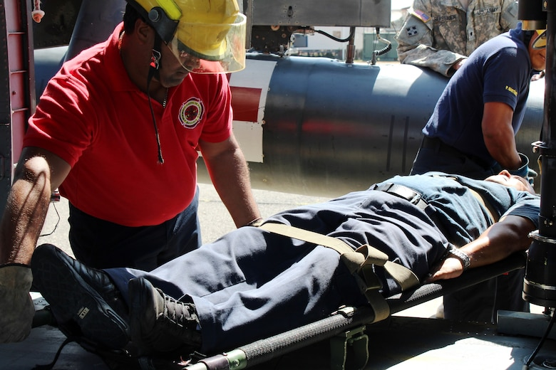 """SOTO CANO AIR BASE, Honduras - Miguel Matus (front center), a firefighter from the Belize National Fire Service, volunteers as the """"victim"""", while his team members load him onto a UH-60 Helicopter during a practice involving the loading and unloading of patients Aug. 27, 2015. This was one event in the week-long CENTAM SMOKE exercise, a quarterly firefighting exercise hosted by Joint Task Force-Bravo at Soto Cano Air Base, Honduras.  (U.S. Army photo by Maria Pinel)"""