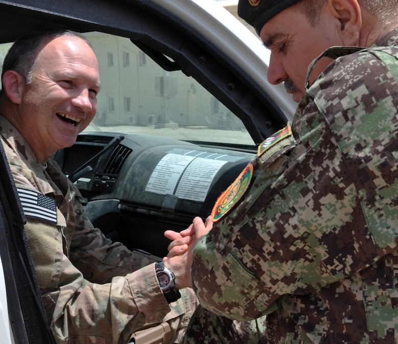 Helmand, Afghanistan (July 25, 2015) - U.S. Air Force Col. Donald Holloway, Resolute Support Advise and Assist Cell-Southwest team lead and ANA 215th Corps G3, Operations Officer Col. Aslum enjoy a moment camaraderie after initial meetings earlier in the day.