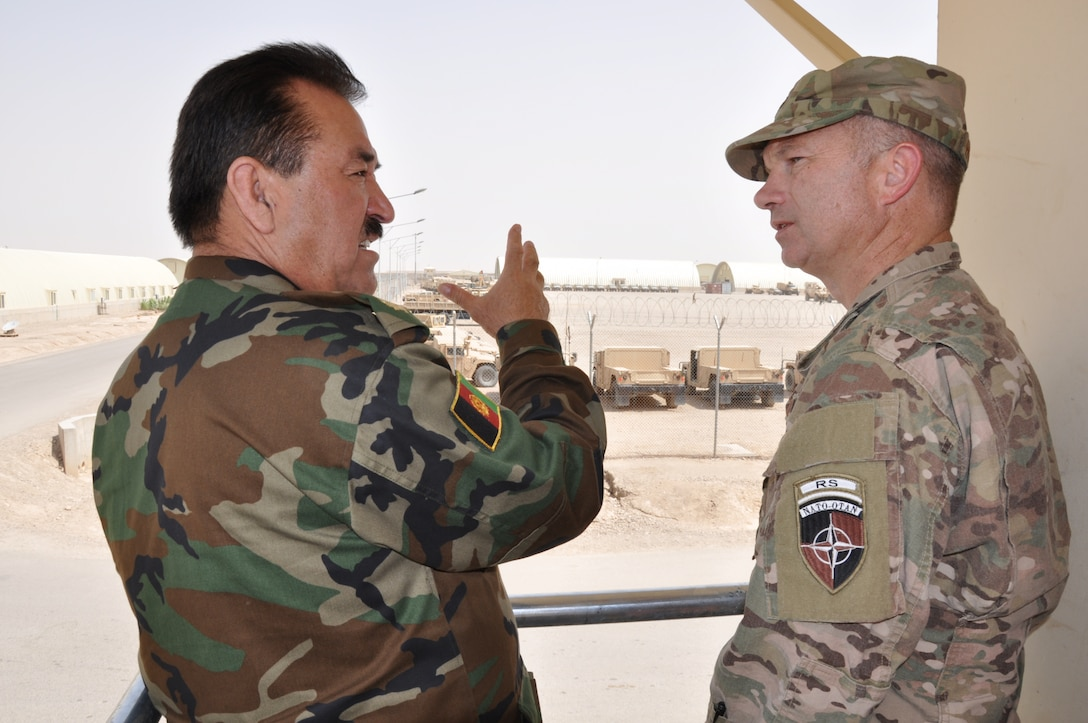 Helmand, Afghanistan (July 25, 2015) - Maj. Gen. Eqbil Ali Afghan Ministry of Defense General Staff, G6, Communications explains to U.S. Air Force Col. Donald Holloway, Resolute Support Advise and Assist Cell-Southwest team lead, how the 215th Corps mobile strike force operates during a demonstration at Camp Shorab, Helmand province Afghanistan.