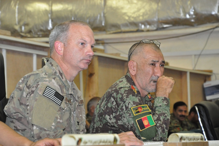 Helmand, Afghanistan (July 25, 2015) - U.S. Air Force Col. Donald Holloway, Resolute Support Advise and Assist Cell-Southwest team lead and ANA 215th Corps Executive Officer, Afghan Brig. General Zamin Hassan listen to the 215th Corps battle update brief for the day.
