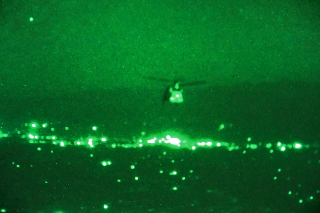 As seen through a night-vision device, a CH-47 Chinook helicopter transports U.S. soldiers and Marines, and Georgian, Czech and Afghan troops to conduct a night patrol outside Bagram Airfield in Parwan province, Afghanistan, Aug. 17, 2015. U.S. Army photo by Sgt. 1st Class David Wheeler