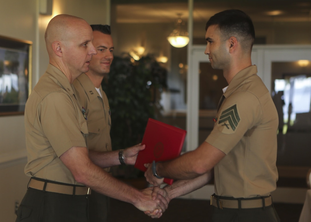 Sgt. Scott Roush, the security chief and senior intelligence analyst for Marine Aircraft Group 26, receives an award congratulating him on his accomplishments as honor graduate of the Squadron Intelligence Training and Certification Course during a graduation ceremony on Marine Corps Air Station New River, Aug. 28, 2015. The students spent 19 training days and more than 90 class hours learning aviation-specific intelligence skills such as structured analytic techniques, comprehensive threat education, capabilities and limitation of all Marine Corps aircraft and how to support a large scale exercise. (U.S. Marine Corps photo by Cpl. Michelle Reif/Released.)