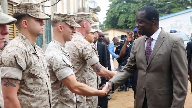 Benin's Minister of Interior Placide Azande greets U.S Marines and sailors, with Special-Purpose Marine Air-Ground Task Force Crisis Response-Africa Detachment A, during an opening ceremony today that officially started training with between the U.S. Marines and sailors and Benin's National Surveillance Police at Benin's Natonal Police Academy in Cotonou, Benin. Today's ceremony marks a new milestone of the partnership between Benin and the U.S. This training is the first time in the Nation Surveillance Police's 10-year history a foreign military has come to train and mentor the specialized unit. Benin's Minister of Interior Placide Azande and U.S. Embassy Benin Chargé d'affaires Todd Whatley were on hand for the ceremony. (Official U.S. Marine Corps photo by Staff Sgt. Bryan A. Peterson)
