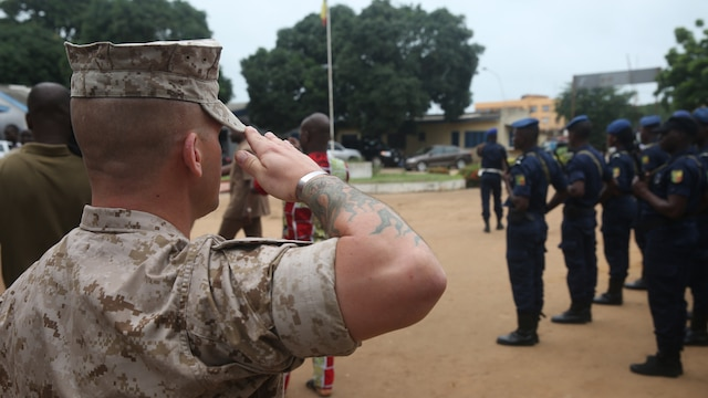 U.S. Marines and sailors, with Special-Purpose Marine Air-Ground Task Force Crisis Response-Africa Detachment A, salute during the Benin national anthem during the opening ceremony Aug. 31, 2015 that officially started training with Benin's National Surveillance Police at Benin's National Police Academy in Cotonou, Benin. Today's ceremony marks a new milestone of the partnership between Benin and the U.S. This training is the first time in the Nation Surveillance Police's 10-year history a foreign military has come to train and mentor the specialized unit. Benin's Minister of Interior Placide Azande and U.S. Embassy Benin Chargé d'affaires Todd Whatley were on hand for the ceremony.