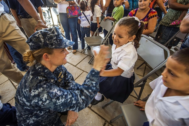 U.S. Navy Capt. Christine Sears, commanding officer of the Medical Treatment Facility on the Military Sealift Command hospital ship USNS Comfort, gives a high-five to a Honduran child during a ceremony to support Continuing Promise 2015 in Trujillo, Honduras, Aug. 29, 2015. The deployment conducts civil-military operations to show U.S. support and commitment to Central and South America and the Caribbean. U.S. Navy photo by Petty Officer 3rd Class Andrew Schneider