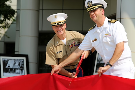 NAVAL STATION GREAT LAKES -- Marine Col. Jason Morris, 9th Marine Corps District commanding officer, and Navy Capt. James D. Hawkins, Naval Station Great Lakes commanding officer, cut the ribbon to officially open the 9th Marine Corps District headquarters building during a ribbon cutting ceremony aboard the Naval Station, Sept. 1, 2015. The ceremony also commemorated the 78th anniversary of the unit's activation as 9th Reserve District, which was established aboard the Naval Station, Sept. 1, 1937. Col. Jason Morris, the District's commanding officer, spoke during the ceremony about the importance of recruiting and how maintaining a well-qualified, well-trained Marine Corps begins with the individual recruiter on the streets. The District is responsible for recruiting enlisted, officer and prior service Marines across 660,000 square miles and 13 states in the Midwest region.