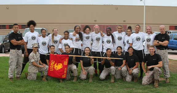 The San Diego State University women's basketball team and Marines from Marine Corps Recruiting Station San Diego pose for a picture following a fitness challenge aboard Marine Corps Air Station Miramar, Calif., Sept. 1, 2015.