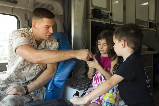 Lance Cpl. Thomas Kurtz, a member of the station special reaction team, shows Amelia and Jackson Morgan, event participants, how to use an intercom at Child Safety Day Event aboard Marine Corps Air Station Iwakuni, Japan, Aug. 27, 2015. Safety personnel shared safety tips with children and demonstrated emergency procedures. (U.S. Marine Corps photo by Lance Cpl. Nicole Zurbrugg/Released)