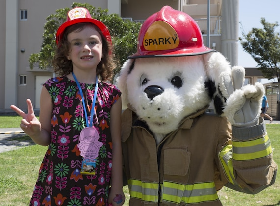 Ava Keller, an event participant, poses with Sparky the Fire Dog at Child Safety Day Event aboard Marine Corps Air Station Iwakuni, Japan, Aug. 27, 2015. The event taught kids a variety of safety tips from how to properly hold a baby and the correct way to wear a back pack, to bicycle safety and household hazards. (U.S. Marine Corps photo by Lance Cpl. Nicole Zurbrugg/Released)