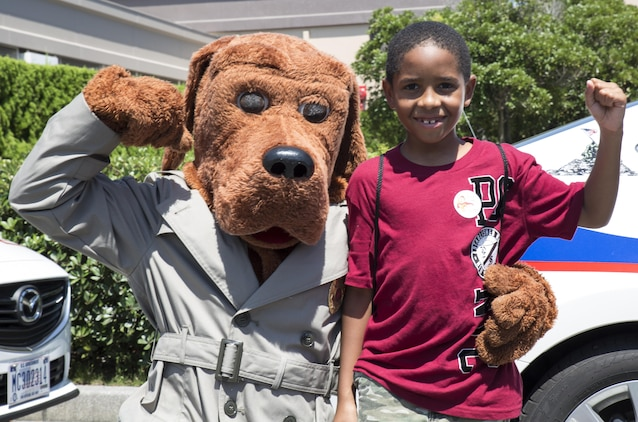 Nehemiah Hinds, an event participant, flexes with McGruff, the Provost Marshal's Office mascot, at Child Safety Day Event aboard Marine Corps Air Station Iwakuni, Japan, Aug. 27, 2015. The event provided kids and parents the opportunity to meet safety officers and learn about staying safe on a daily basis. (U.S. Marine Corps photo by Lance Cpl. Nicole Zurbrugg/Released)