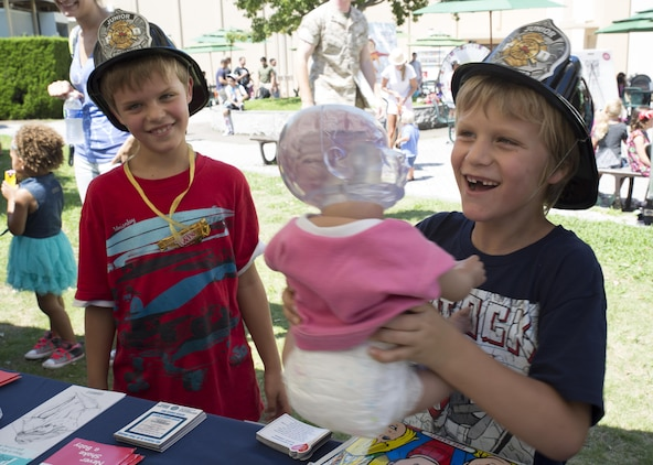 Kennon Lowry, left, and Jackson Lowry learn how to properly hold a baby at Child Safety Day Event aboard Marine Corps Air Station Iwakuni, Japan, Aug. 27, 2015. The doll's head lights up to demonstrate the parts of the brain that are affected when an infant is shaken or not properly supported. The event helped kids learn personal safety through interactive activities and games. (U.S. Marine Corps photo by Lance Cpl. Nicole Zurbrugg/Released)