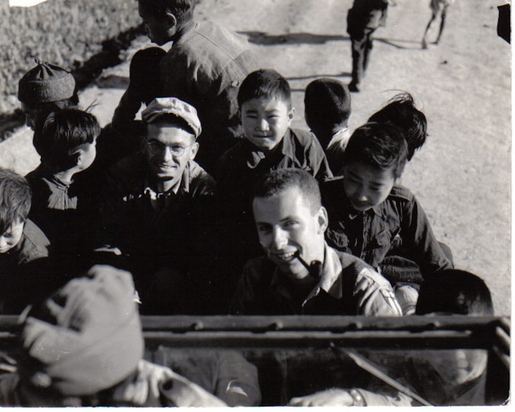 """S/Sgt John Brasko (left, a Pennsylvania Air Guardsman before and after the war) and 1st Lt. Arthur Clark (who remained on active duty and became a Major General) smile for the camera as Clark drives a jeep with accompanying as young Chinese citizens at Chengkung Airfield in China, circa early 1945.  They served with """"G"""" Flight of the 35th Photo Recon Squadron at several different forward airfields.  (Courtesy Mr. John Brasko, Jr.)"""