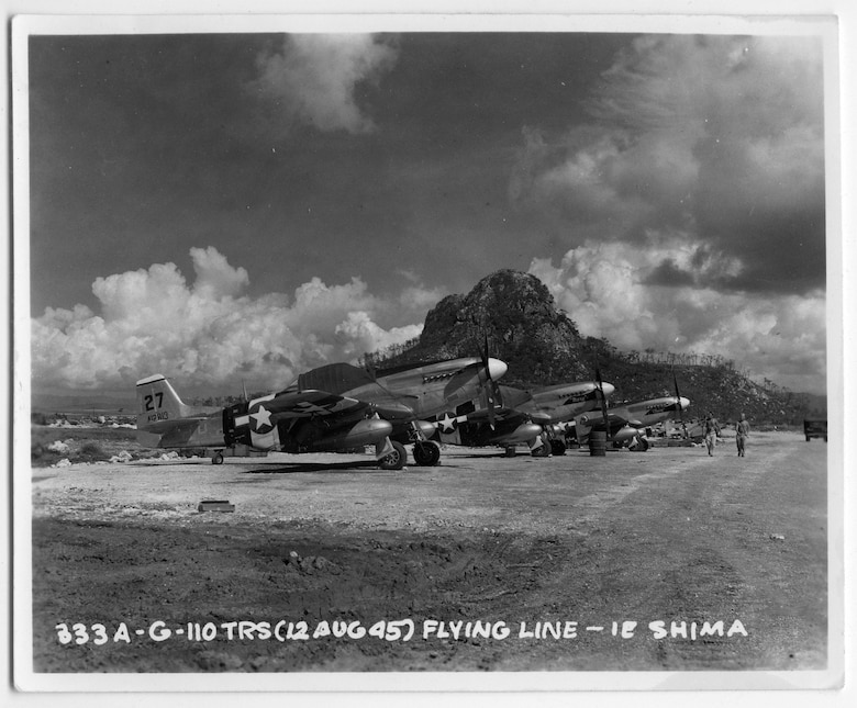 F-6D Photo Mustangs of Les Donis' 110th Tactical Reconnaissance Squadron rest in the shadow of the volcanic cone on Ie Shima 12 August 1945, a week before the arrival of the white-painted BETTY bombers on the small island.  (US Army via Mr. John Donis)